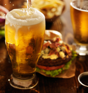 Photo of beer being poured into a tall glass with a hamburger in the background.
